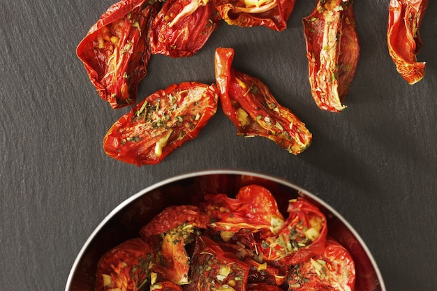 Sliced red tomatoes dried in the sun with garlic and italian spices on dark surface
