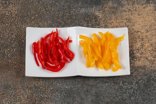 Peperoni rossi e gialli affettati sulla zolla bianca.