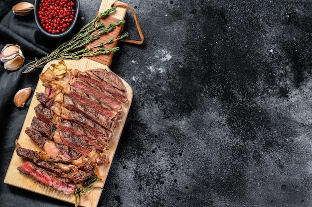 まな板にスライスしたリブアイステーキ、ミディアムレア。黒の背景。上面図。コピースペース