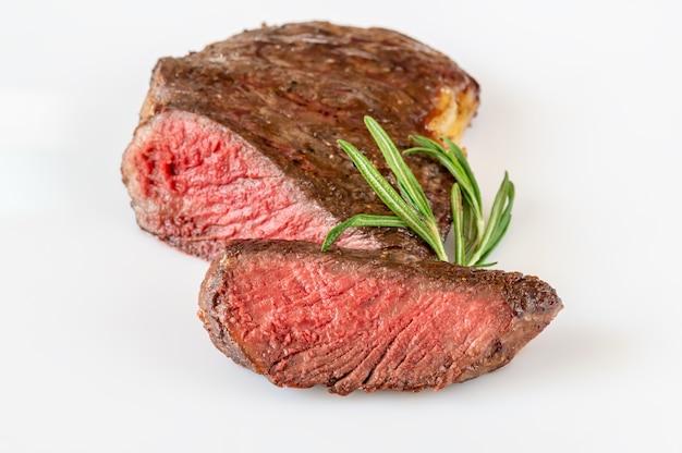 Sliced rib eye steak on white surface