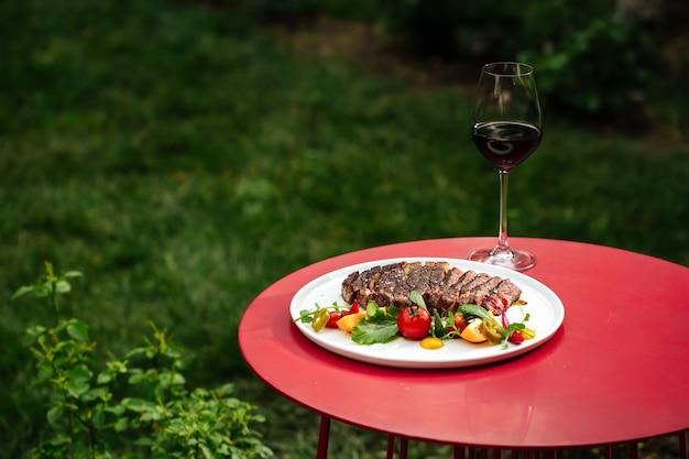 赤い丸テーブルに新鮮な野菜のサラダと赤ワインを添えたスライスしたリブアイビーフステーキ