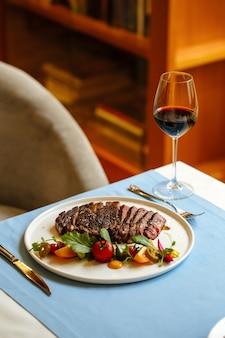 青いテーブルの上に新鮮な野菜のサラダとスライスしたリブアイビーフステーキ
