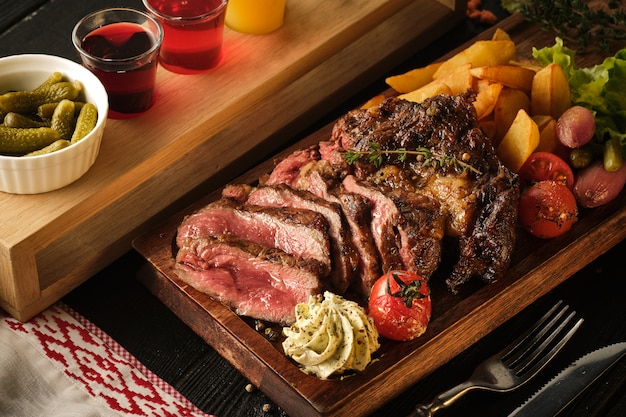 Sliced ribeye steak with potatoes, onions and baked cherry tomatoes
