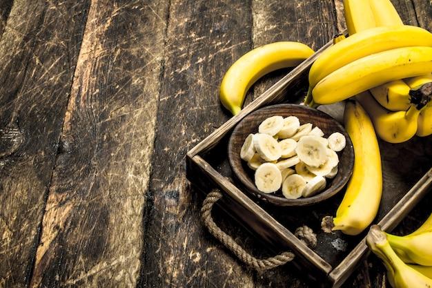 熟したバナナをボウルにスライスしました。木製の背景に。