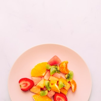 Sliced ripe fresh tropical fruits on plate