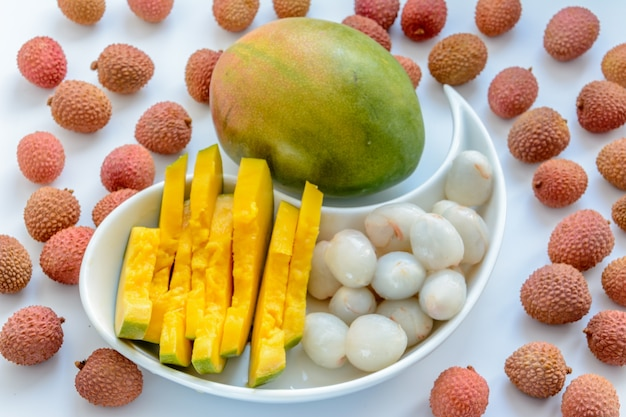 Нарезанные спелые манго в окружении спелых плодов личи на тарелке на белом фоне. спелый личи без скорлупы.