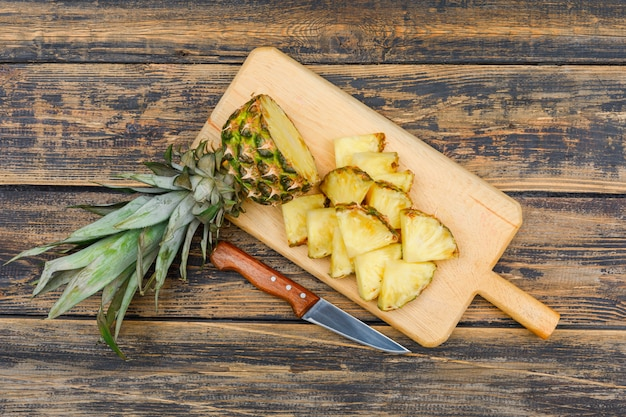 Sliced ripe pineapple in a cutting board with a fruit knife top view on a wood grunge surface