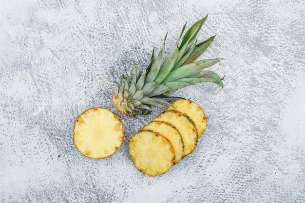 Отрезанный зрелый ананас на поверхности grunge, взгляд сверху.