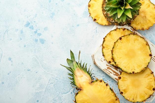 Нарезанный спелый ананас на светло-синем каменном фоне. тропические фрукты. вид сверху. свободное место для текста.