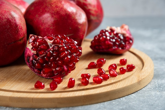 Sliced ripe pomegranate on a wooden board.