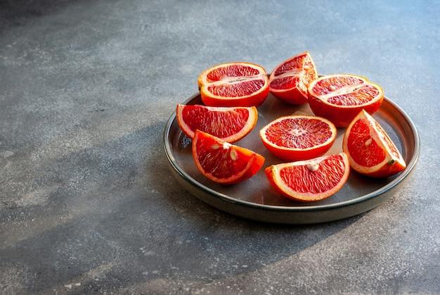 熟したシチリア産ブラッドオレンジを皿にスライス