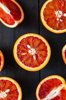 暗い木製の背景にスライスした熟したシチリアブラッドオレンジ、クローズアップ