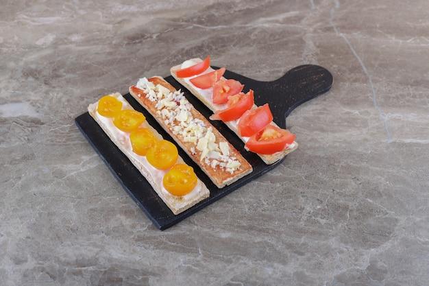 Pomodori maturi e acerbi affettati su pane croccante sul tagliere, sulla superficie del marmo