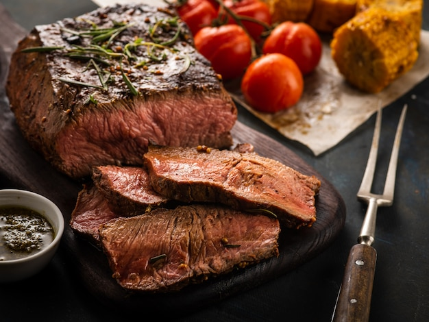 Sliced roast beef on cutting board with grilled vegetables.