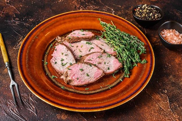 Нежный стейк из вырезки из ростбифа на деревенской тарелке
