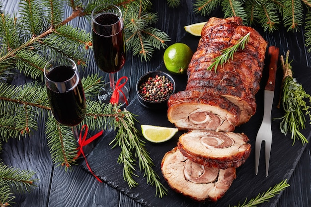 Sliced roast pork roulade -  porchetta, delicious pork roast of italian culinary holiday tradition on a slate tray with fir-tree and red wine, close-up, authentic recipe