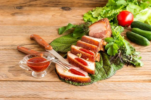 케첩과 녹색 야채와 함께 제공되는 나무 테이블에 구운 바베큐 양지머리를 얇게 썬 것입니다.