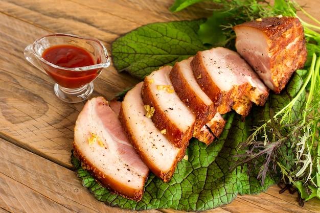 Нарезанная жареная грудинка барбекю на деревянном столе подается с кетчупом и зелеными овощами.