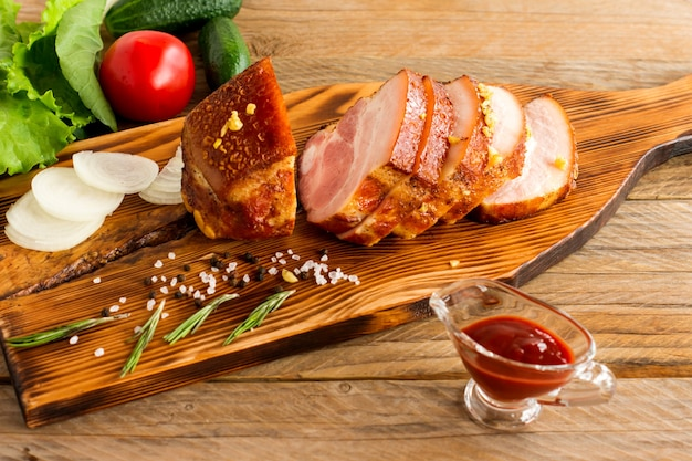 Sliced roasted bbq brisket on a wooden table served with ketchup and green vegetables.
