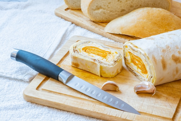 Sliced roll of armenian pita bread with carrot filling on a wooden board. on the board are cloves of garlic and a knife.