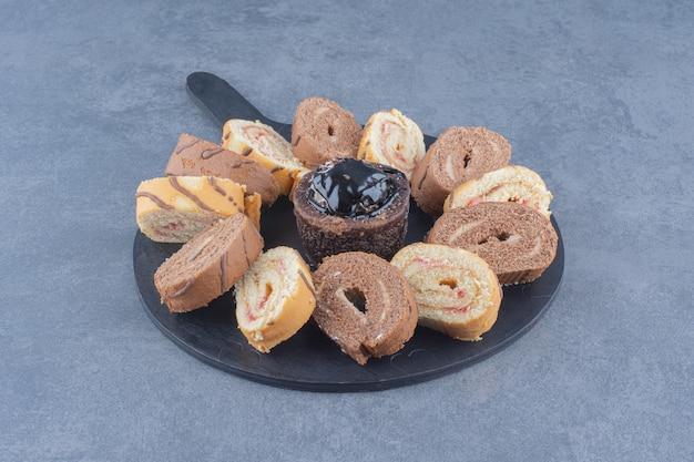 大理石の背景に、ボード上のスライスされたロールケーキ。