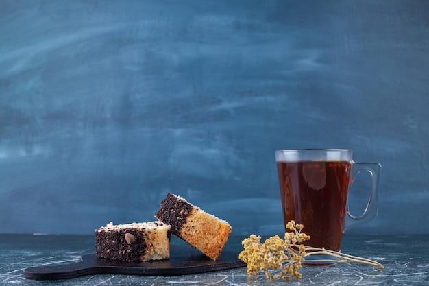 Нарезанный рулет торт на деревянной доске с чашкой чая на каменном фоне.