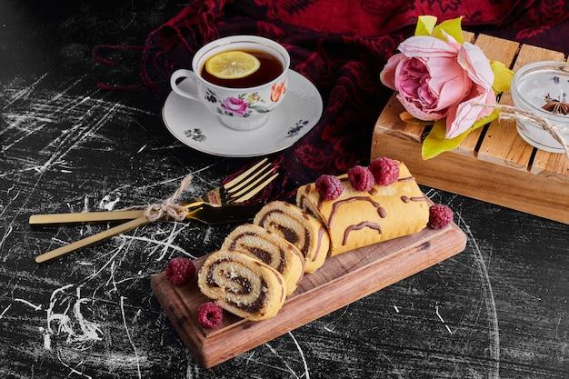 Rotolo di torta a fette con ripieno di cioccolato servito con una tazza di tè.