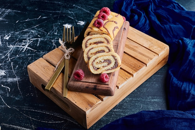 Sliced roll cake with chocolate filling on a wooden tray.