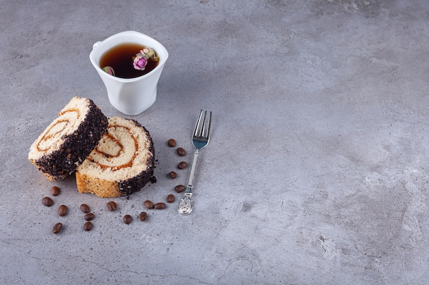 Sliced roll cake with coffee beans and cup of tea on stone background.