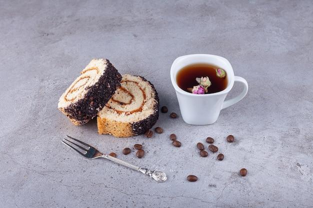 Torta a fette di rotolo sulla tavola di legno con una tazza di tè sulla superficie di pietra.