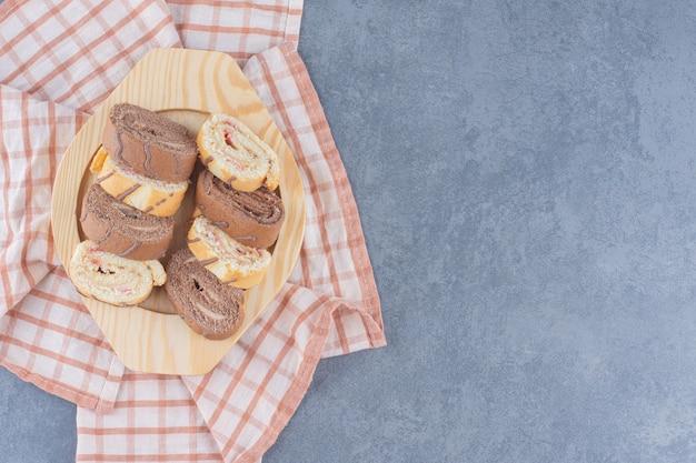 대리석 배경에 수건에 보드에 롤 케이크를 슬라이스.