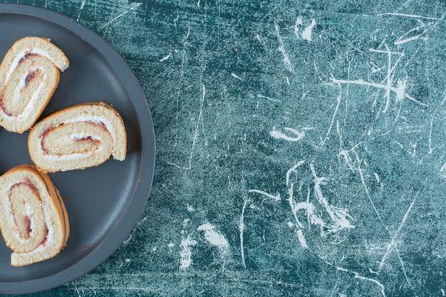 파란색 배경에 팬에 얇게 썬 롤 케이크. 고품질 사진