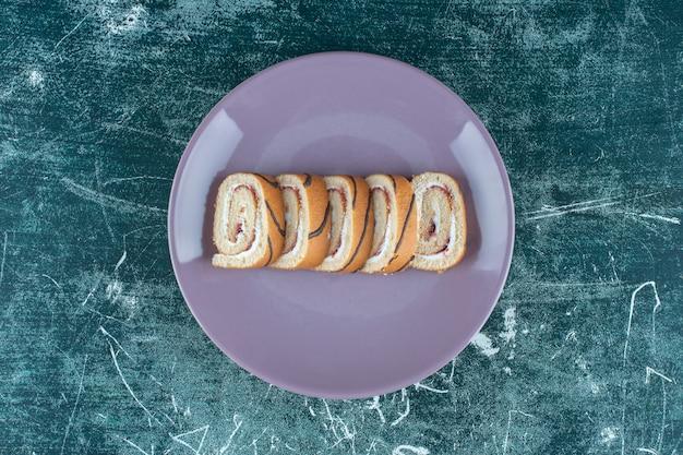 파란색 배경에 접시에 얇게 썬 롤 케이크. 고품질 사진