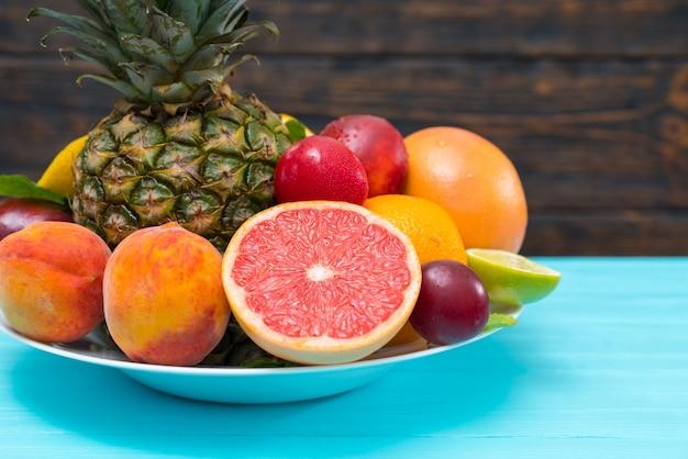 Нарезанный рубиновый грейпфрут на тарелке тропических фруктов