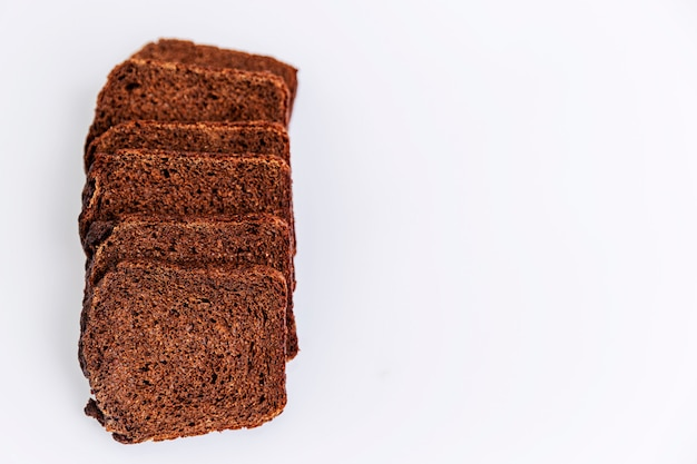 Sliced russian borodino brown bread on a white background. healthy eating and traditions. close-up. top view. space for text.