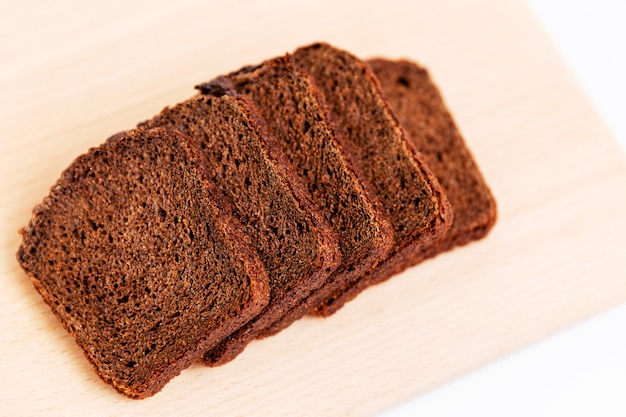 Sliced russian borodino brown bread on a white background. healthy eating and traditions. close-up. top view.