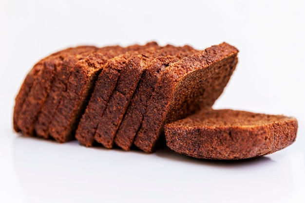 Sliced russian borodino brown bread on a white background. healthy eating and traditions. close-up.