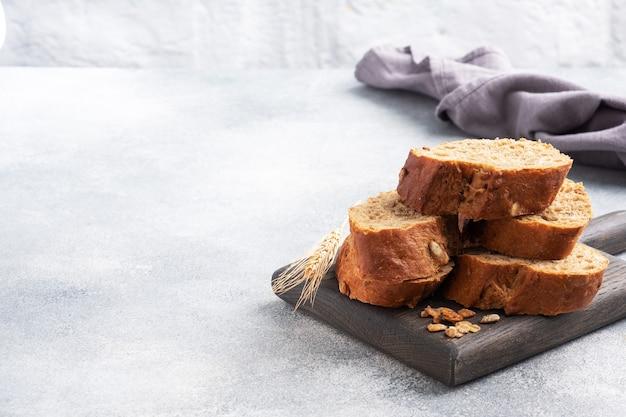シリアルと灰色の背景にスライスしたライ麦バゲット。全粒粉パン、健康食品のコンセプト。スペースをコピーします。