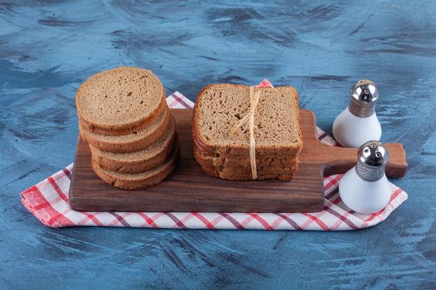 Pane di segale a fette su una tavola su un asciugamano, sulla superficie blu.
