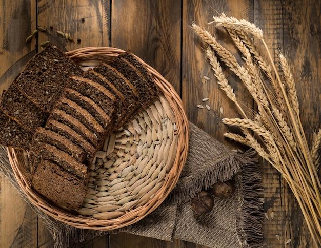고리버들 쟁반에 얇게 썬 호밀 빵과 나무 표면에 작은 이삭