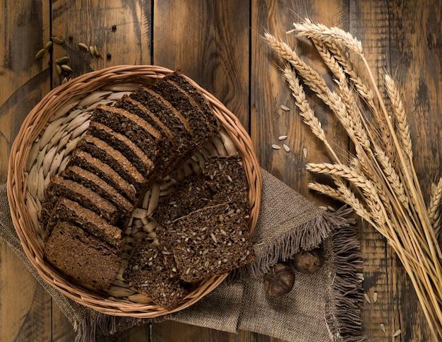 Нарезанный ржаной хлеб в плетеном лотке и колоски на деревянной поверхности