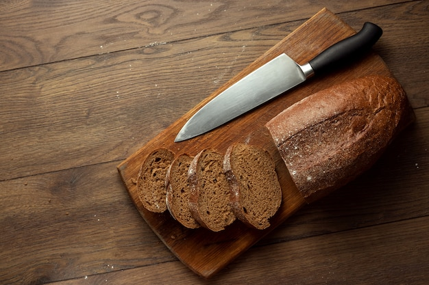Sliced rye bread and a knife close-up, on a wooden cutting board