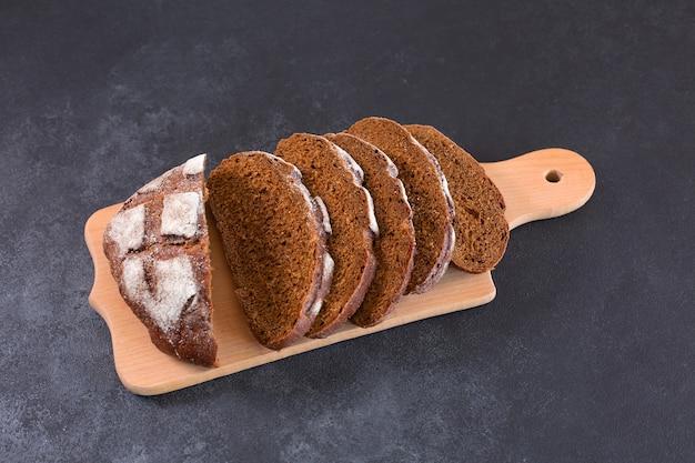 컷티그 보드와 검은 테이블에 얇게 썬 호밀 빵