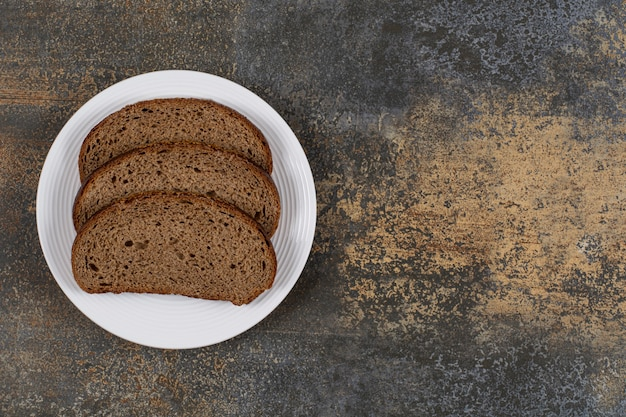 Нарезанный ржаной хлеб на белой тарелке