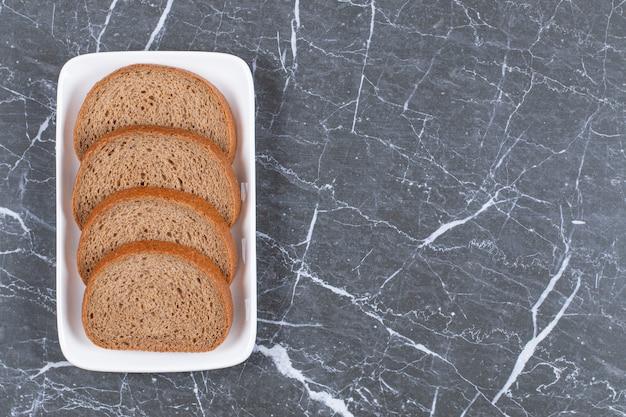Sliced rye bread on white plate over grey.