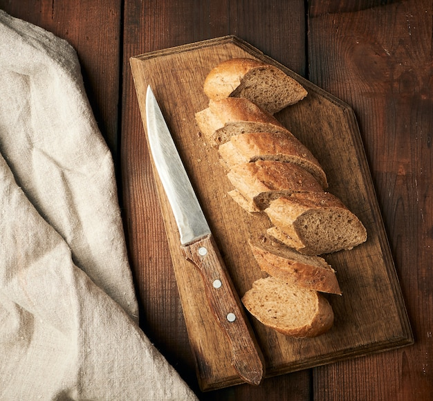 Sliced rye flour baguette on a wooden cutting board