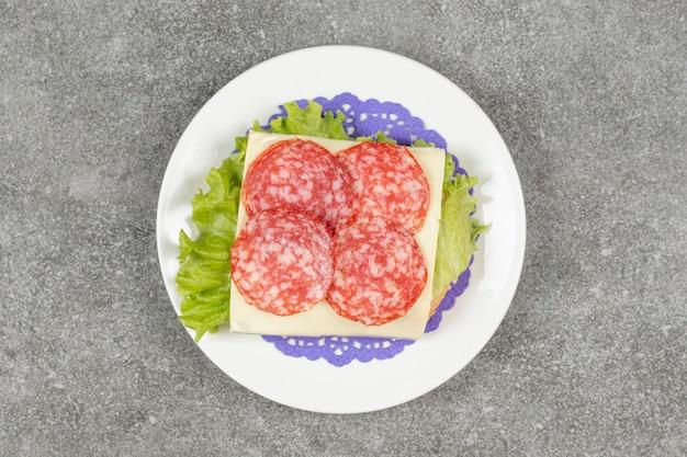 Нарезанная салями на белой тарелке с сыром и листьями салата
