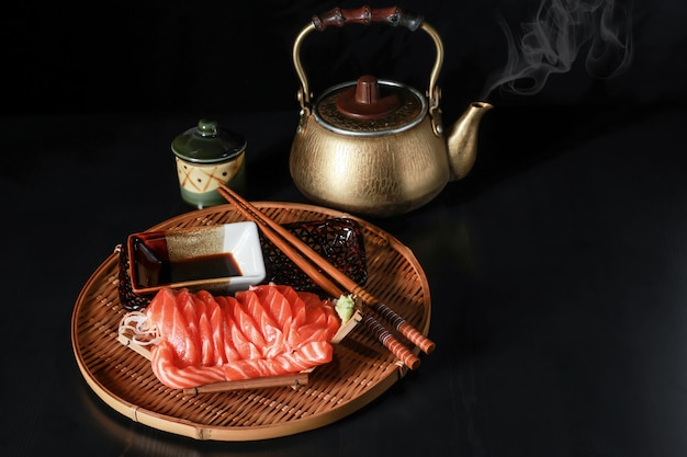 Sliced salmon fish sashimi in the boat on the black wooden table.