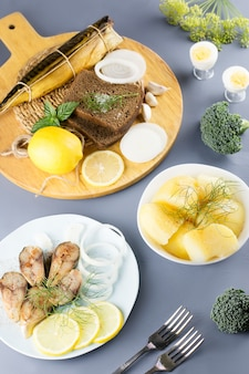 Sliced salted fish with lemon and seasoning, boiled potatoes on a table