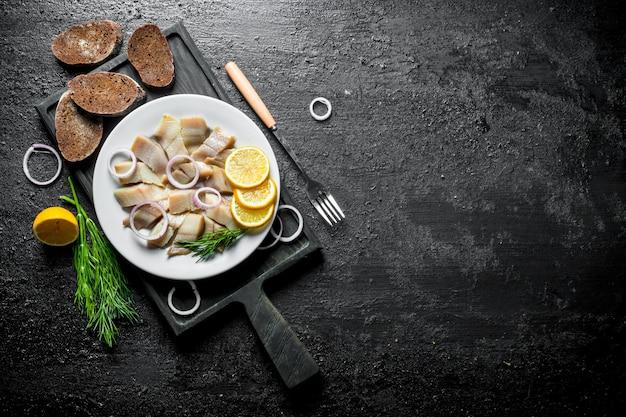 Нарезанная соленая сельдь на разделочной доске с черным хлебом, лимоном и укропом. на черной деревенской поверхности